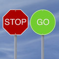 Stop go signs against blue sky background Stock Photos