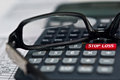 Stop loss calculator a with a button with reading glasses on financial report Royalty Free Stock Photo