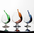Stop motion colored liquids in glasses on mirror Royalty Free Stock Photo