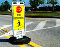 Stop for pedestrians road crossing sign a marks a crosswalk in an office parking lot Royalty Free Stock Images