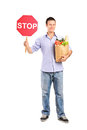 Stop and shop here full length portrait of a male holding a paper bag and a stop road sign isolated on white background Royalty Free Stock Photo