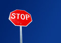 Stop sign bright red with blue sky background Royalty Free Stock Photo