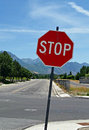 Stop sign at a street intersection with mountains and trees in background Stock Photography