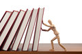 Stopping domino effect figurine trying to stop a caused by the falling books Stock Photo