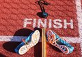 Stopwatch, baton and spikes at finish line Royalty Free Stock Photo