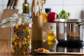 Storage Jar with Colorful Pasta and Cooking Spoon on Worktop Royalty Free Stock Photos