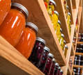 Storage shelves with canned goods on wooden in pantry Royalty Free Stock Photography