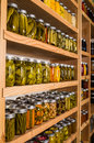 Storage shelves with canned goods on wooden in pantry Stock Photo