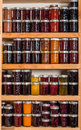 Storage shelves with canned goods on wooden in pantry Royalty Free Stock Photo
