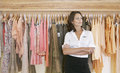 Store Assitant Standing by Hanging Clothes in Store Royalty Free Stock Photos