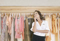 Store Assitant Standing by Hanging Clothes in Store Royalty Free Stock Photo