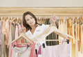 Store Assitant Working and Hanging Clothes in Store Stock Photo