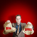 Store discount promotion big sale sales man holding large brown paper shopping bags with text on red copy space background Stock Images