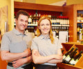 Store manager and saleswoman happy smiling in wine shop Royalty Free Stock Images