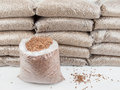 Store of wood pellets an open bag with a stack bagged in storage behind Royalty Free Stock Image