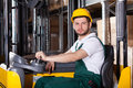 Storehouse employee driving on forklift during in warehouse Royalty Free Stock Image