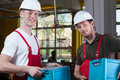 Storekeepers holding crates with finished goods happy Royalty Free Stock Photos