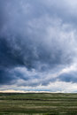 Storm clouds above field of green grass Royalty Free Stock Photo