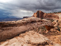 Storm clouds gather in desert storms and rain begins to fall the distance the red rock canyons and mesa arch of canyonlands Stock Photography