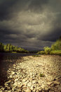 Storm clouds over the river photo Stock Photos