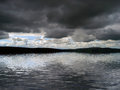 Storm clouds over water dark stormy hang simulated Stock Images