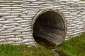 Storm culvert drainage pipe concrete revetment large circular water or infrastructure with bank reinforcement Stock Photo