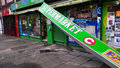 Storm damage shop banner london to ripped off the facade and hanging down after in night before the christmas eve cricklewood Royalty Free Stock Image