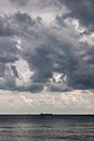 Before a storm huge clouds hung over the dark lifeless sea Stock Image
