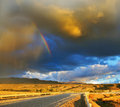 Storm over the pampas low swirling cloud and flat plain covered in orange sunset cloud crosses rainbow in steppe runs a gravel Royalty Free Stock Photo