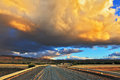 Storm over the pampas in steppe runs a gravel road enormous cloud and a flat plain covered in orange sunset Royalty Free Stock Photos