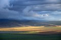 Storm sky and sun gaps on the fields hills horizon Stock Photos