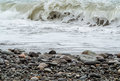 Storming sea and pebbly shore Stock Images
