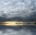 Stormy evening landscape clouded with reflective water surface at time Royalty Free Stock Images