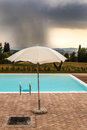 Stormy pool a parasol near the edge of a swimming and a storm in the background Royalty Free Stock Images