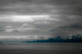 Stormy skies from the bay of alaska cloudy evening over distant mountains over calm cold waters Stock Photo