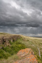 Stormy sky at head smashed in landscape of a buffalo jump heritage site Royalty Free Stock Photo