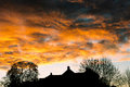 Stormy sunset clouds storm at with buildings and trees silhouetted against the sky shropshire england uk Stock Photography