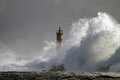 Stormy waves big wave against lighthouse in the north of portugal in a overcast evening mouth of river ave in vila do conde Stock Photo
