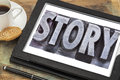 Story word in metal type a grunge letterpress on a digital tablet with a cup of coffee Royalty Free Stock Photo