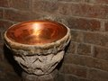 Stoup inside the church in a copper vase ancient holy water font Stock Photos