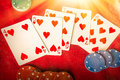 Straight flush beams of heavenly light illuminate a winning hand of hearts Royalty Free Stock Image