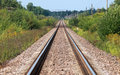 Straight railway perspective with poles green grass and blue sky Stock Photo