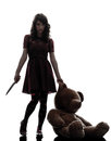 Strange young woman killer holding bloody knife silhouette one caucasian an teddy bear in white background Stock Photos