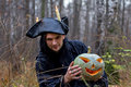 Stranger with covered face keeps pumpkin on his hands in the forest Royalty Free Stock Image
