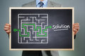 Strategy business businessman holding a blackboard planning and finding a solution through a chalk drawing of a maze Royalty Free Stock Photo