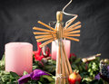 Straw angel on an advent wreath photo of a with pink candles Stock Image