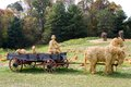 Straw animals with wagon driver and made of sit in a old farm pulled by horses in a pumpkin patch Royalty Free Stock Image