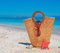 Straw bag sunglasses starfish and shells by the shore Royalty Free Stock Photography