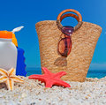 Straw bag and suntan lotion at the beach Stock Images