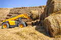 Straw bale stack lifting machine and storage lift tractor machinery in farm yard Royalty Free Stock Images